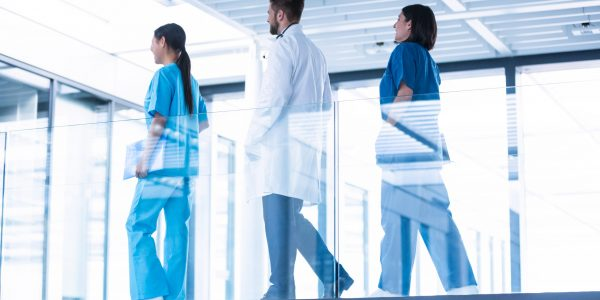 Doctor with nurses walking in corridor in hospital